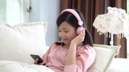 rests : Beautiful Asian girl listening to music  sitting on a sofa in the living room at home slow motion Stock Footage
