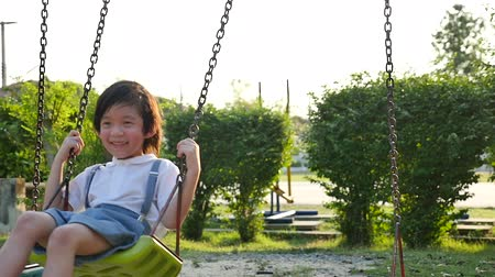 невинный : Cute Asian child having fun on swing in the park slow motion