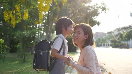 urlop : Asian mother  saying goodbye to her son as he leave for School,back to school concept