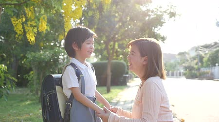 elsődleges : Asian mother  saying goodbye to her son as he leave for School,back to school concept