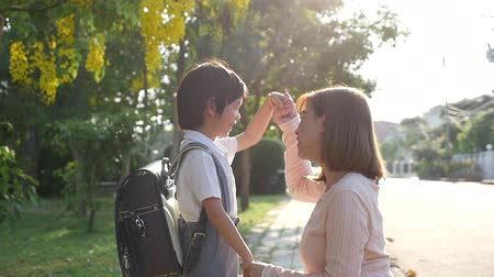 cuidadoso : Asian mother  saying goodbye to her son as he leave for School,back to school concept
