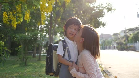 learning to walk : Asian mother  saying goodbye to her son as he leave for School,back to school concept