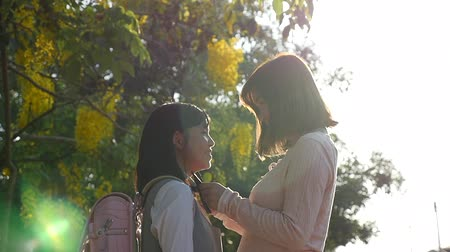 klasa : Asian mother talking her daughter with backpack outdoors, back to school