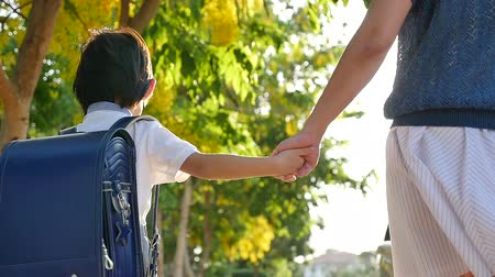 okula geri : Asian mother holding hand of little son with backpack outdoors, back to school slow motion Stok Video