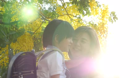 first person : Asian mother holding her son while walking in the park , back to school concept slow motion