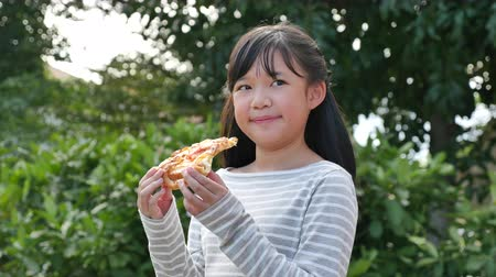 měsíců : Beautiful Asian girl eating eating pizza outdoor slow motion