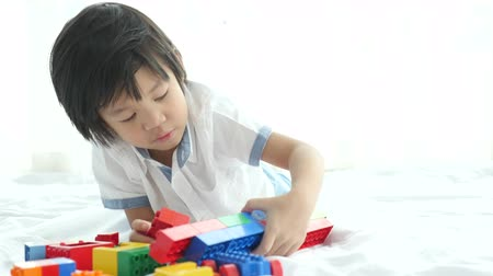 przedszkolak : Little asian child playing with colorful construction blocks on white bed