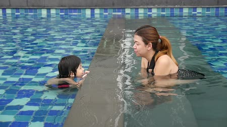 anne : Asian Mother and son playing in swimming pool slow motion