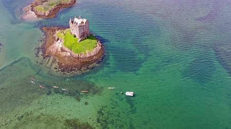 argyll : Canoes gathering around medieval Castle Stalker on the west coast of Scotland by Appin