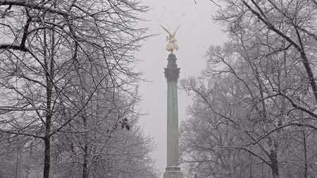 pozlacený : Munich  Germany - February 17 2018 : The Angel of Peace on the top of Friedensengel monument in Munich, Germany during the snow srorm