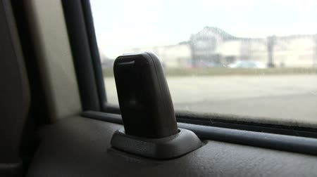 odemknout : Car door locking knob going up and down as it is being triggered. Moving cars in background.