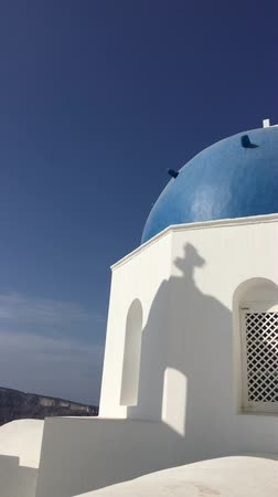 УВР : 4k video, the view of the classic blue roof church, white architecture of Oia village on Santorini island, Greece
