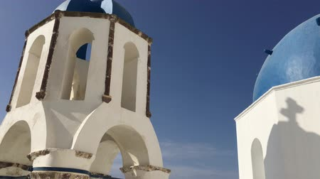 řek : 4k video, the view of the classic blue roof church, white architecture of Oia village on Santorini island, Greece