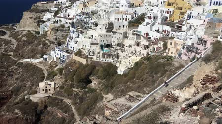 УВР : 4k video. amazing romantic white houses in Oia, Santorini island, Greece. with a panoramic view of the whole cliff