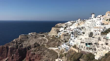 řek : 4k video. amazing romantic white houses in Oia, Santorini island, Greece. with a panoramic view of the whole cliff