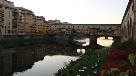 Time lapse of sunset on Ponte Vecchio in Florence, with street lamps light reflections in the water.