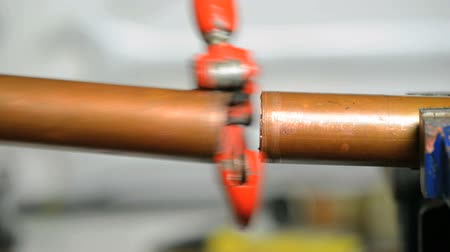 plumber : plumber cutting a copper pipe