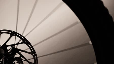 bicycle : Still shot of closeup silhouette of bike wheel turning. Transition Stock Footage