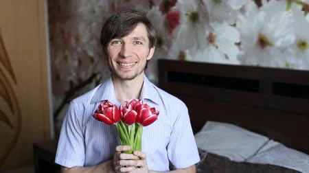 carinho : Beautiful man with affection presents flowers to the camera - the tulips.