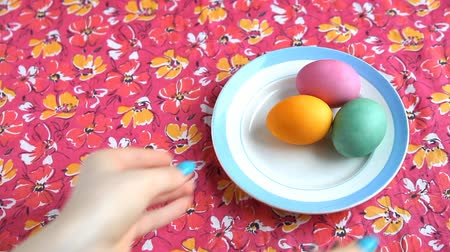 truly : She puts on a pink tablecloth saucer with colorful Easter eggs. Stock Footage