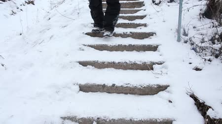 fall down : Man falling down the broken stairs. Man is walking down the broken stairs covered with snow. He slips and falls down Stock Footage