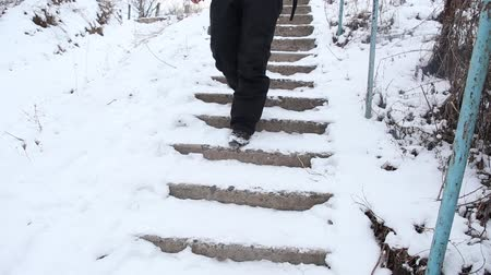 queda de neve : Man carefully walking down the broken stairs covered with snow