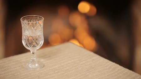 semillon : Glass with vodka on a background of a burning fireplace
