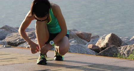 бегун трусцой : Healthy lifestyle fitness woman runner tying shoelace before running on sunny seaside