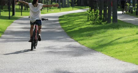 raised : Woman riding a bike on sunny park trail with arms outstretched Stock Footage