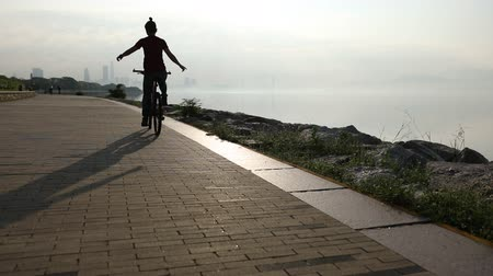 raised : Hands free cycling woman Riding Bike on Seaside Road At Sunrise With Arms outstretched