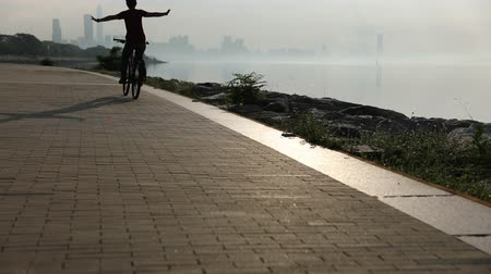 Çapraz kollar : Hands free cycling woman Riding Bike on Seaside Road At Sunrise With Arms outstretched