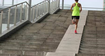 kimerül : Young woman runner sportswoman climbing up city stairs jogging and running in urban training workout Stock mozgókép