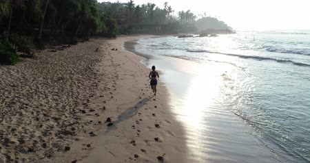 дубленый : Healthy lifestyle young woman running on tropical beach during sunrise in the morning