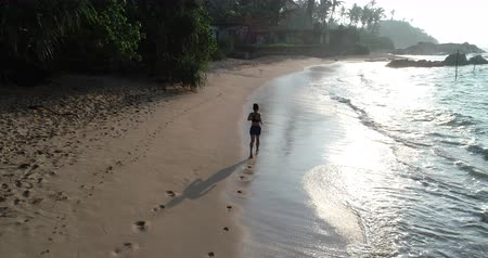 életerő : Healthy lifestyle young woman running on tropical beach during sunrise in the morning