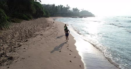 életerő : Two healthy lifestyle young women friends running on tropical beach during sunrise in the morning, aerial footage