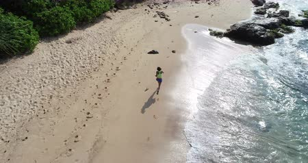 életerő : Young woman running on tropical beach  aerial drone view footage Stock mozgókép
