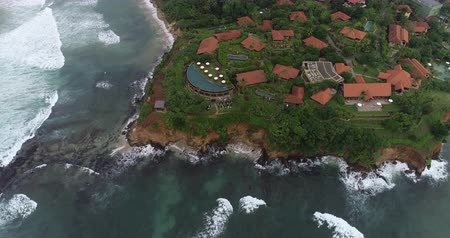шри : Aerial view.Drone ascent aerial footage of ocean waves and fishermen village landscape