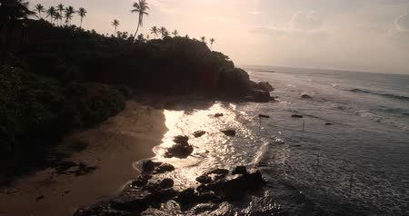 Aerial view.Drone ascent aerial footage of ocean waves and weligama cap in the sunrise landscape