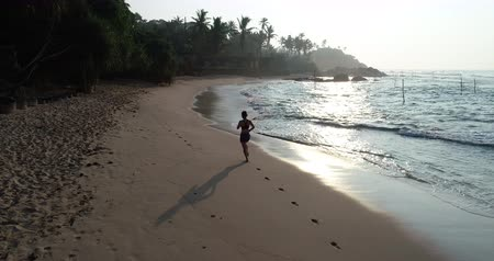 ślady stóp : Healthy lifestyle young woman running on tropical beach during sunrise in the morning