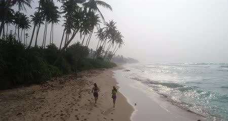 hátsó megvilágítású : Two healthy lifestyle young women friends running on tropical beach during sunrise in the morning, aerial drone view footage