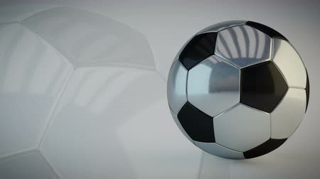 Rotating glossy soccer ball on white background - seamless looping