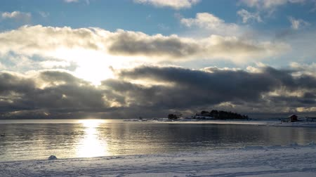 Timelapse of clouds passing over bay and snow covered beach in winter