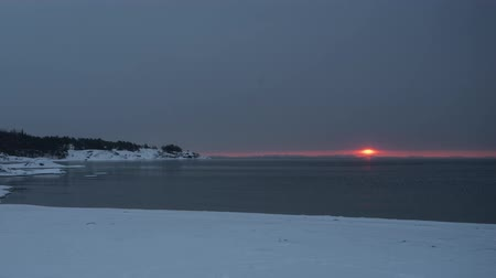 Timelapse of sunrise during light snow on snowy beach in Hanko, Finland Stock Footage