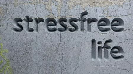 animation of stressfree life word carved in a gray wall