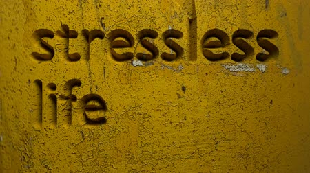 animation of stressless life word carved in a yellow wall