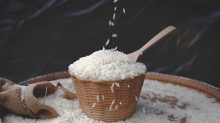 ジャスミン : Throwing Jasmine rice with wooden basket background, White rice falling down.