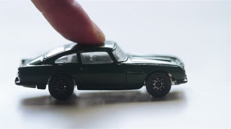 broken crash : closeup sideview of a green toy car being pushed by a finger and hitting another pink one out of the frame Stock Footage