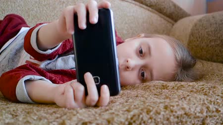 Teen girl playing in the phone while lying on the couch.