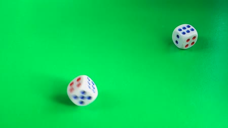 White dice rolling on a green gaming table.