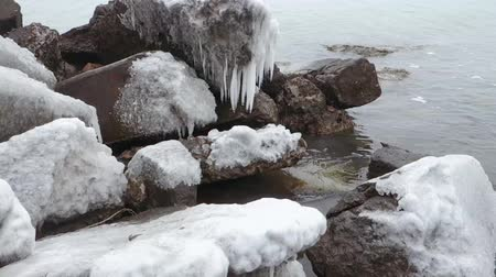 Stones on the sea covered with ice and with hanging icicles from them.
